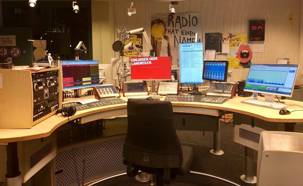 Ein Radiostudio mit Mischpulten, Mikrofonen, Kopfhörern und mehreren Monitoren